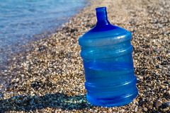 A large water bottle stands on the beach, stock photos