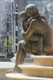 Large water fountain and bronze sculptures of adults and childre Stock Photos