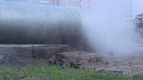 A large water pipe has burst and thick steam is coming out.A broken hot water or heating pipe.Urban communications and drainage sy