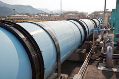 Large water pipe in a sewage treatment plant. With digestion tanks in the background Stock Photography