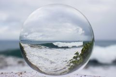 Large Wave at Beach Taken Through Glass or Crystal Ball stock photo