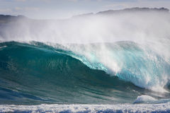 Large wave breaking with spray Stock Photos