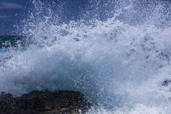 Large wave breaking on volcanic rock Royalty Free Stock Images