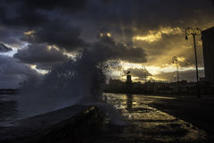 Large wave crashing over the malecon in havana at sunrise. A large wave is crashing over the malecon sea wall with magical rays of sunrise coming through the Royalty Free Stock Image