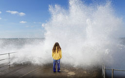 Tsunami wave over person. Large wave smashes over coastal defense as a person with dreadlocks stands there in this refreshing / refreshment or tsunami concept royalty free stock photo