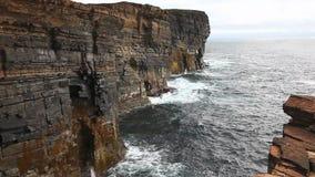 Large waves crash against rock cliffs in Orkney stock footage