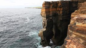 Large waves crash against sea cliffs in Orkney, Scotland stock video