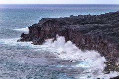 Waves crashing against tall volcanic cliff on Hawaii`s Big Island, spray in the air. Pacific ocean in the background. Large waves crashing against tall volcanic stock images