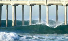 Large waves crashing underneath the Huntington Beach Pier in Orange County California. Large powerful waves crashing underneath the Huntington Beach Pier in stock image
