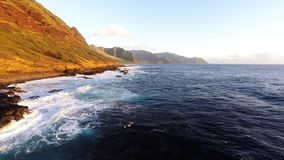 Large waves roll into the north west coast of Oahu. Aerial view of large waves rolling into the picturesque north west coast of Oahu along the Kaena Point hiking stock footage