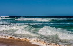 Large waves rolling in to the beach from a turqoise sea under a blue sky.  stock photo
