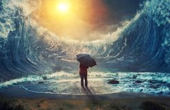 Large waves and woman. A woman surrounded by large waves and holding an umbrella stock photos