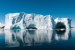 Large weathered iceberg with caves reflected in glassy water, Cierva Cove, Antarctic Peninsula royalty free stock image