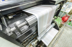 A large webset offset printing press. Running a long roll off paper over its rollers at high speed stock images
