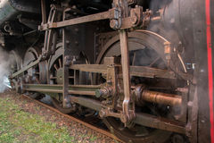 Large wheels steam train on tracks. The mechanical part of the steam train on tracks Royalty Free Stock Photography