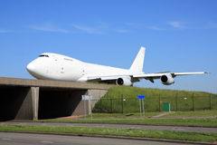 Large white aircraft crossing bridge Royalty Free Stock Photo