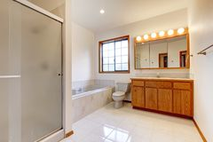 Large white bathroom with tub, shower and wood cabinet. Large white bathroom with tub, shower, shiny tiles and wood cabinet stock photography