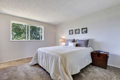 Large white bed in simple bedroom with carpet floor. Stock Photography
