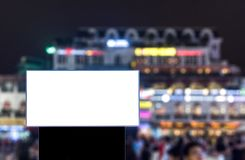 Large white billboard rectangle shape on downtown square. At night Stock Photography