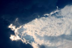 Large white and black puffy clouds in the sunset sky seem to swallow the sky. Stock Photos