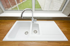 Large white ceramic kitchen sink. Kitchen detail of a large white cermaic kitchen sink with a chrome faucet and solid wooden worktop royalty free stock photo