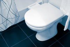 Large white and ceramic toilet seat fixture. Shower, curtain. White Bathrobe on a hanger stock photos