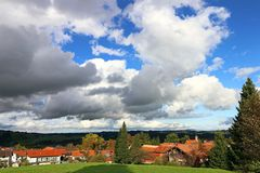 Large white clouds in the blue sky above a village in Bavaria Stock Photo