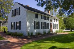 Large White Colonial Home. White clapboard colonial home on main street of historic New England town.  Displays red barn board door and black shutters with Stock Images