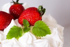 Large white delicious cake with cream and decorated with strawberries and mint on a transparent stand on a gray background stock photography