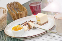 Large white dish, creamy cheesecake with mango sauce. Bright bokeh background. Basket with Cutlery, white napkins, coffee Cup, sug Royalty Free Stock Photo