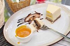 Large white dish, creamy cheesecake with mango sauce. Bright bokeh background. Basket with Cutlery, white napkins, coffee Cup, sug Royalty Free Stock Photos