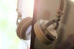 Large white female headphones and laptop. So close, toned image stock photography