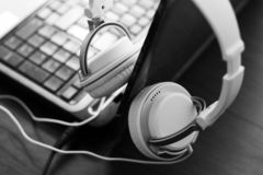 Large white female headphones and laptop. So close, black and white stock photography