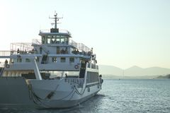 A large white ferry floats away into the distance. Water trail. Stock Images