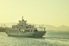 A large white ferry floats away into the distance. Water trail. Stock Photo