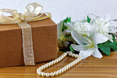 Large white flower, brown wrapped gift Royalty Free Stock Photos