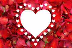 Large white heart surround with smaller hearts on dried rose petal background Royalty Free Stock Photo