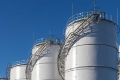 Large white Industrial tanks for petrol and oil. Fuel tanks at the tank farm. Big Industrial oil tanks in petroleum storage terminal.Large white Industrial royalty free stock photos