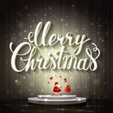 Large white lettering Merry Christmas. Santa Claus juggles with gifts on the stage. Royalty Free Stock Images