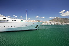 Large, white, luxurious and expensive yacht. Moored up in port or harbor in sunny spain with blue sky and mountain background Royalty Free Stock Photography