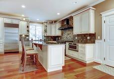 Large white luxury kitchen with cherry hardwood. Royalty Free Stock Photo