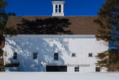 Large white New England barn in a snowy field aganst a deep blue late winters sky. White cupola on roof, multiple 6X3 and 2x3 pane windows, flanked by large Royalty Free Stock Photography