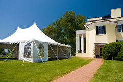 Large white party tent. Set up for a wedding on a front lawn of a large mansion Royalty Free Stock Image
