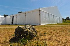 Large white party tent if a field. A huge tent in a grass field under sunny sky Royalty Free Stock Photography