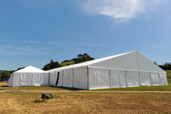 Large white party tent if a field. A huge tent in a grass field under sunny sky Royalty Free Stock Photos