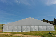 Large white party tent if a field. A huge tent in a grass field under sunny sky Stock Photo