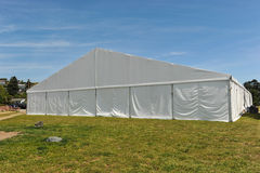 Large white party tent if a field. A huge tent in a grass field under sunny sky Stock Photos