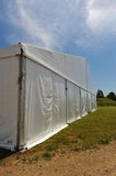 Large white party tent if a field. A huge tent in a grass field under sunny sky Royalty Free Stock Photo