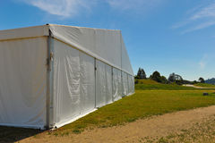 Large white party tent if a field. A huge tent in a grass field under sunny sky Stock Image