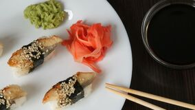 A large white plate on which lies four huge sushi with eels rewound with a piece of nori next to pink ginger and green. Large white plate on which lies four huge stock video